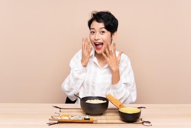 Joven asiática en una mesa con tazón de fideos y sushi con expresión facial sorpresa