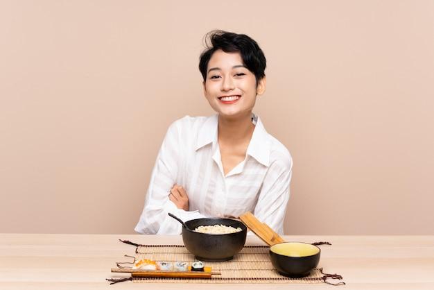 Joven asiática en una mesa con tazón de fideos y sushi riendo