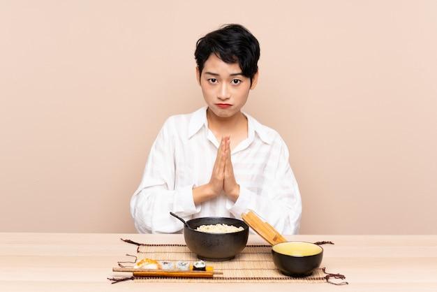 Joven asiática en una mesa con tazón de fideos y sushi suplicando