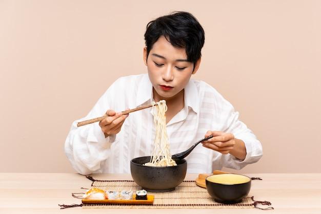 Joven asiática en una mesa con tazón de fideos y sushi