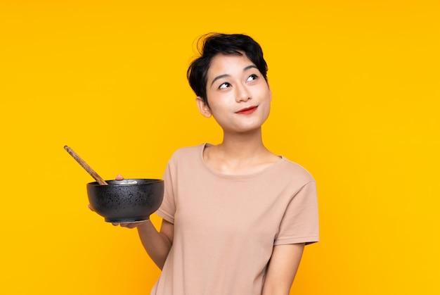 Joven asiática mirando hacia arriba mientras sonríe mientras sostiene un tazón de fideos con palillos