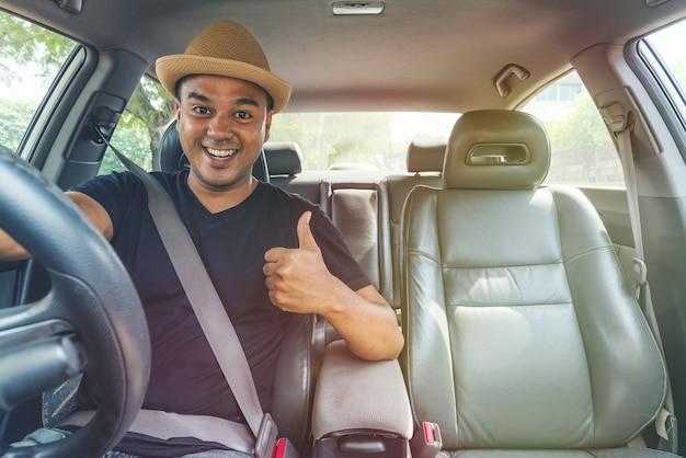 Joven asiática mostrando el pulgar hacia arriba mientras conduce el auto