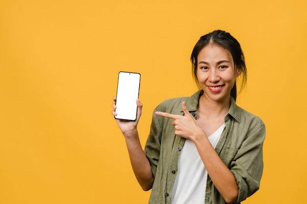 Joven asiática muestra la pantalla vacía del teléfono inteligente con expresión positiva, sonríe ampliamente, vestida con ropa informal sintiendo felicidad en la pared amarilla. teléfono móvil con pantalla blanca en mano femenina.