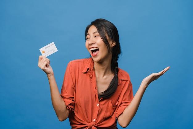 Joven asiática muestra una tarjeta bancaria de crédito con expresión positiva, sonríe ampliamente, vestida con ropa informal sintiendo felicidad y parada aislada en la pared azul. concepto de expresión facial.