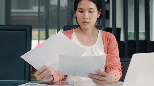 Joven asiática mujer embarazada registros de ingresos y gastos en el hogar. niña mamá feliz usando presupuesto récord portátil, impuestos, documentos financieros, comercio electrónico trabajando en la sala de estar en casa.