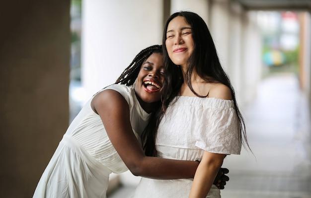 Joven asiática y mujeres afro abrazándose y riendo juntos en el concepto de gente diversa y al aire libre.