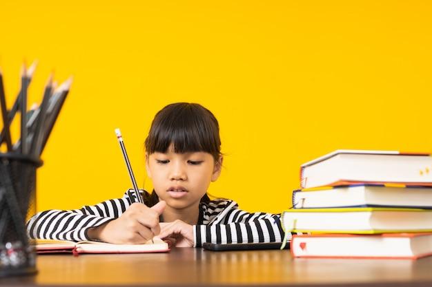 Joven asiática, niña tailandesa escribiendo y nota sobre la mesa con fondo amarillo