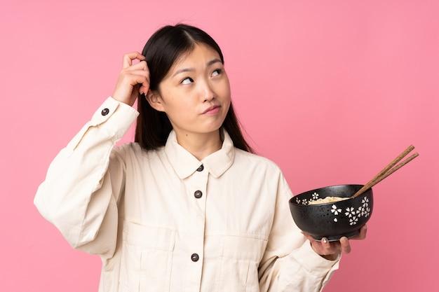 Joven asiática en pared rosa con dudas y con expresión de la cara confusa mientras sostiene un tazón de fideos con palillos