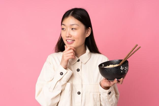 Joven asiática en pared rosa pensando en una idea y mirando hacia el lado mientras sostiene un tazón de fideos con palillos