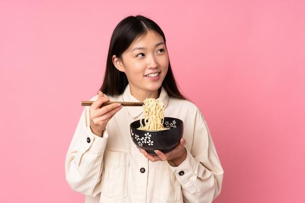 Joven asiática en pared rosa sosteniendo un tazón de fideos con palillos y mirando hacia arriba