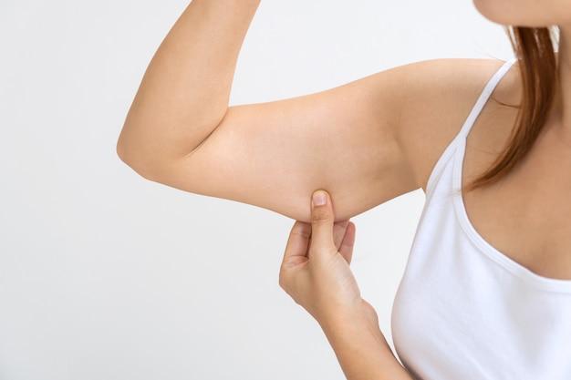 Joven asiática pellizcando la piel suelta o flacidez en la parte superior del brazo en la pared blanca