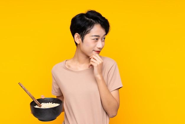Joven asiática pensando en una idea y mirando de lado mientras sostiene un tazón de fideos con palillos