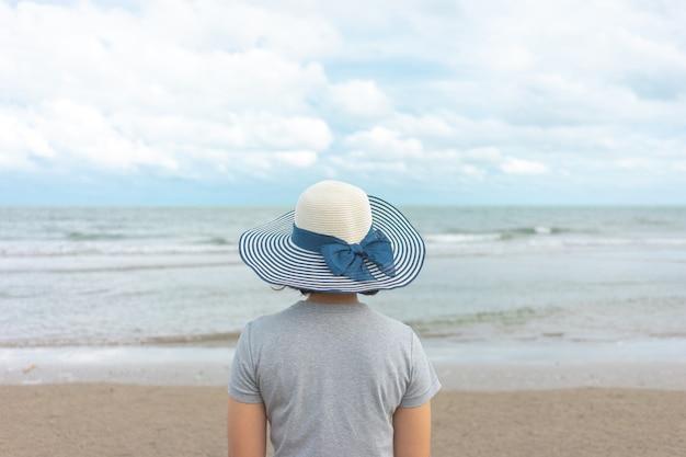 Joven asiática de pie frente al mar.