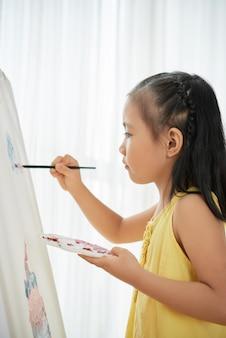 Joven asiática de pie en el interior frente a caballete y cuadro de pintura
