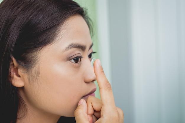 Joven asiática poniendo lentes de contacto en el ojo derecho