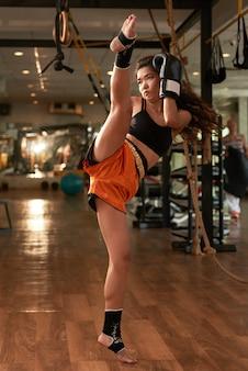 Joven asiática practicando boxeo muay thai en un gimnasio