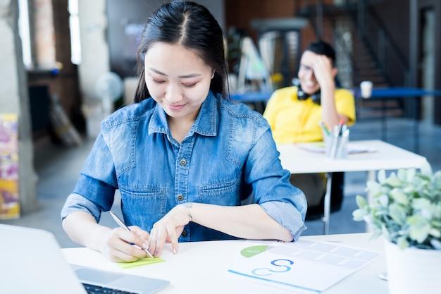 Joven asiática que trabaja en la oficina moderna