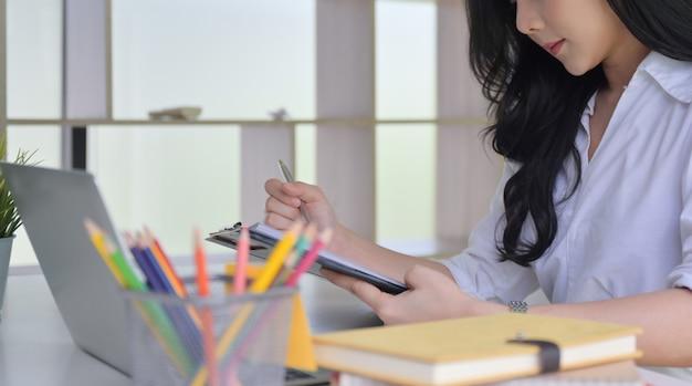 Joven asiática que trabajaba en la oficina, miró los documentos en la mano con la computadora portátil y los suministros de oficina en el escritorio.