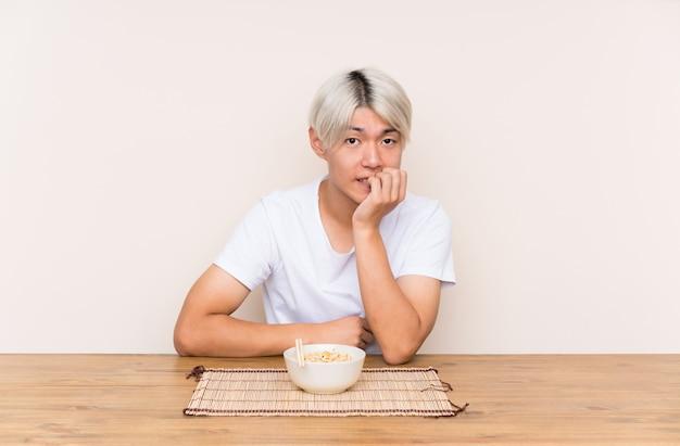 Joven asiática con ramen en una mesa nervioso y asustado