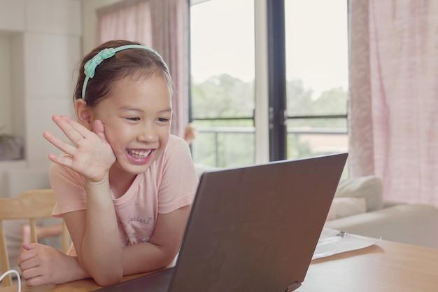 Joven asiática de raza mixta que hace videollamadas presenciales con una computadora portátil en casa, usando la aplicación en línea de aprendizaje de zoom, distanciamiento social, aislamiento, educación en el hogar, aprendizaje remoto