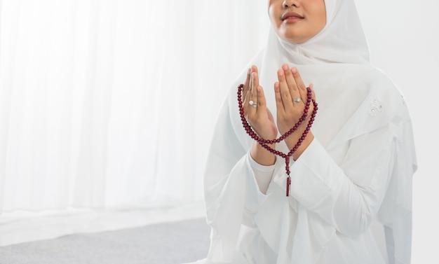 Joven asiática rezando con al-qur'an y rosarios