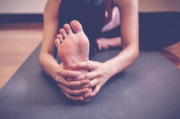 Joven asiática sana practicando clase de yoga