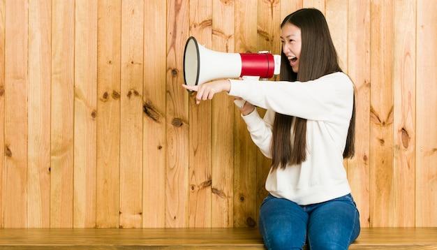 Joven asiática sentada y hablando a través de un megáfono