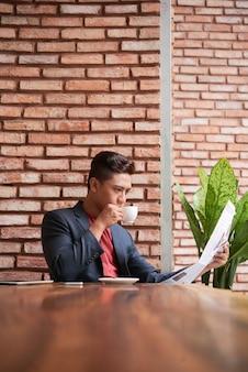 Joven asiática sentada a la mesa en el loft cafe, tomando café y leyendo el periódico