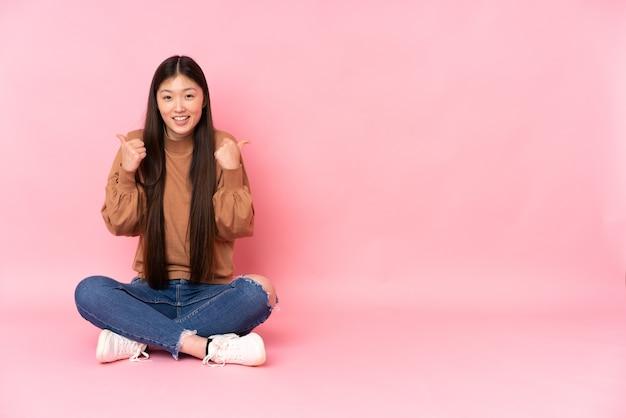 Joven asiática sentada en el suelo