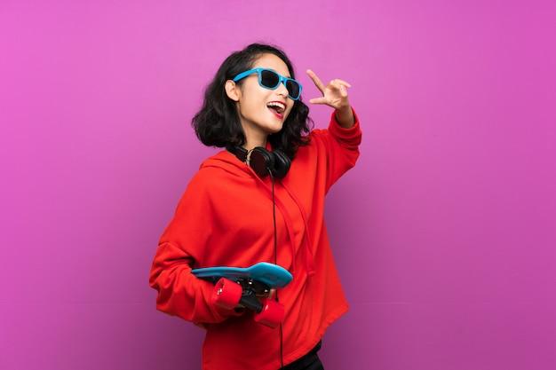 Joven asiática con skate sobre pared púrpura