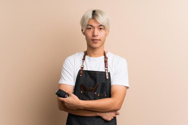 Joven asiática sobre aislado con peluquería o vestido de barbero y sosteniendo la máquina de corte de cabello