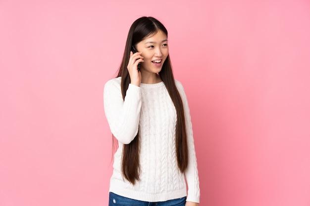 Joven asiática sobre pared aislada manteniendo una conversación con el teléfono móvil