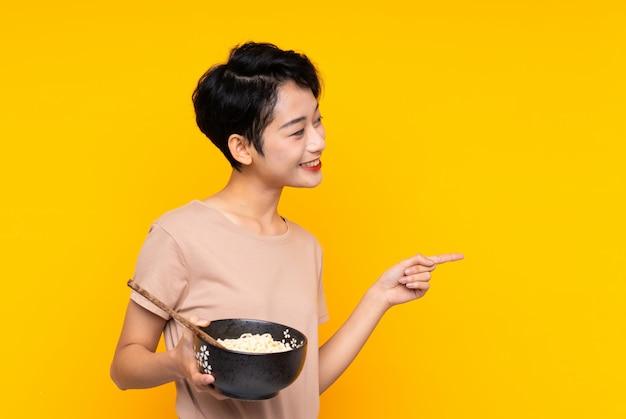 Joven asiática sobre pared amarilla aislada apuntando hacia un lado para presentar un producto mientras sostiene un tazón de fideos con palillos