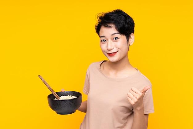 Joven asiática sobre pared amarilla aislada con los pulgares hacia arriba porque algo bueno ha sucedido mientras sostiene un tazón de fideos con palillos
