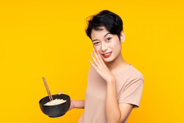 Joven asiática sobre pared amarilla aislada susurrando algo mientras sostiene un tazón de fideos con palillos
