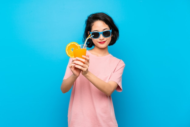 Joven asiática sobre pared azul aislada sosteniendo un cóctel