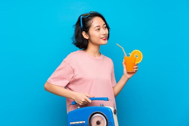 Joven asiática sobre pared azul aislada sosteniendo una radio
