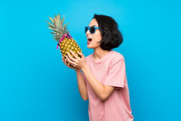 Joven asiática sobre pared azul aislado sosteniendo una piña con gafas de sol