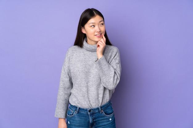 Joven asiática sobre pared pensando en una idea mientras mira hacia arriba
