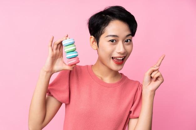 Joven asiática sobre pared rosa aislada con coloridos macarons franceses y apuntando hacia una gran idea