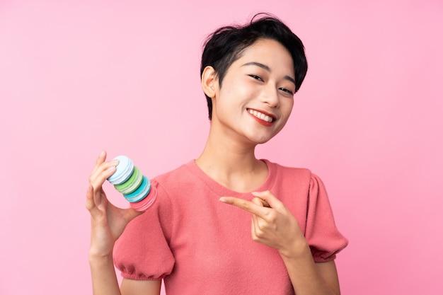 Joven asiática sobre pared rosa aislada con coloridos macarons franceses y apuntando