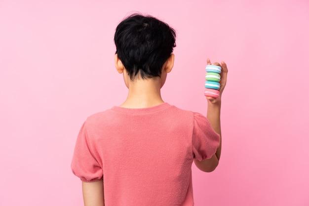 Joven asiática sobre pared rosa aislada con coloridos macarons franceses en posición posterior