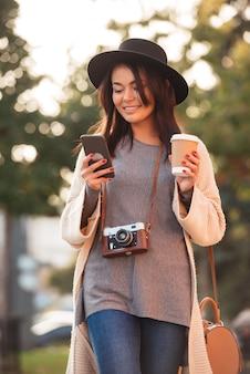 Joven asiática en sombrero negro enviando mensajes de texto sms en teléfono móvil y sosteniendo la taza de café, mientras camina en el parque de la ciudad