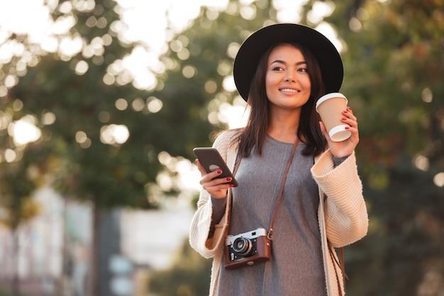 Joven asiática en sombrero negro tomando café y sosteniendo el teléfono móvil mientras camina en el parque al aire libre