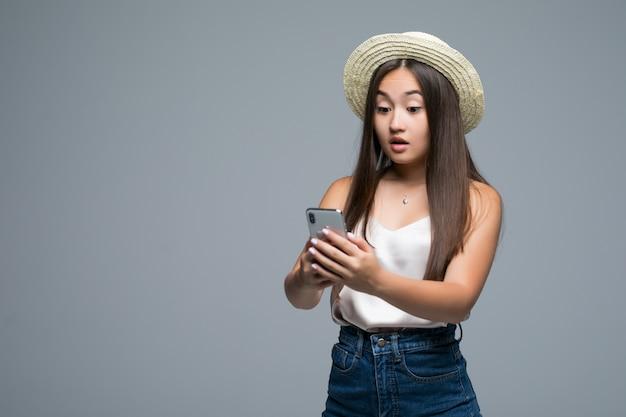 Joven asiática con sombrero de paja usar teléfono sobre fondo gris