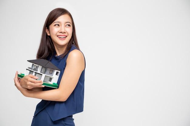 Joven asiática sonriendo y abrazando el modelo de muestra de la casa de sus sueños