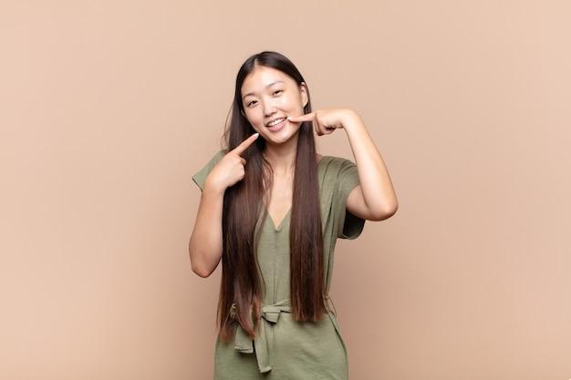 Joven asiática sonriendo con confianza apuntando a su propia sonrisa amplia, actitud positiva, relajada y satisfecha