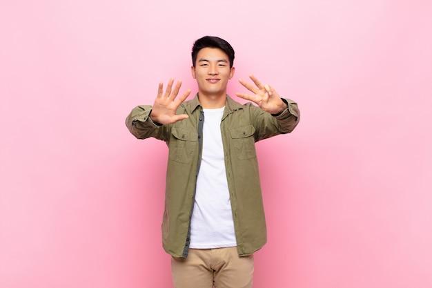 Joven asiática sonriente y amigable, mostrando el número ocho u octavo con la mano hacia adelante, contando hacia atrás sobre la pared de color