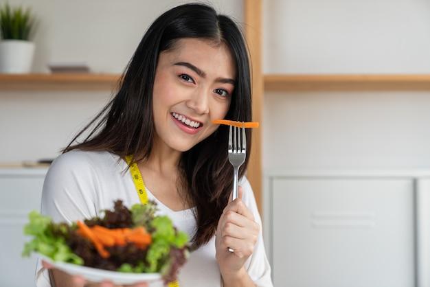 Joven asiática sonriente perder peso comiendo ensalada de verduras en platos en su mano, concepto de dieta y buena salud