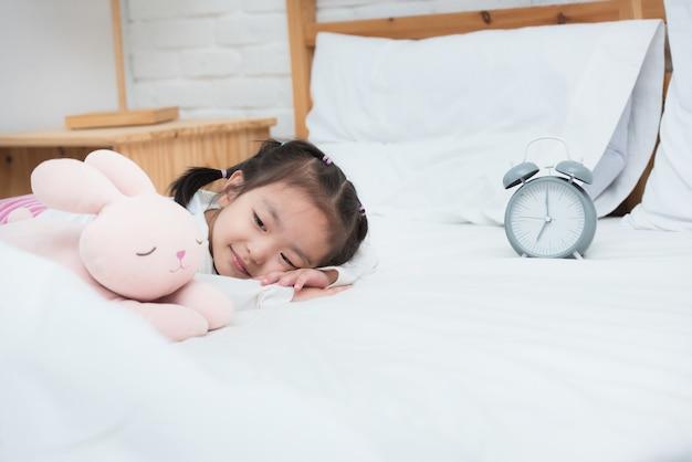 La joven asiática sonriente yacía en la cama con el reloj despertador y la muñeca.